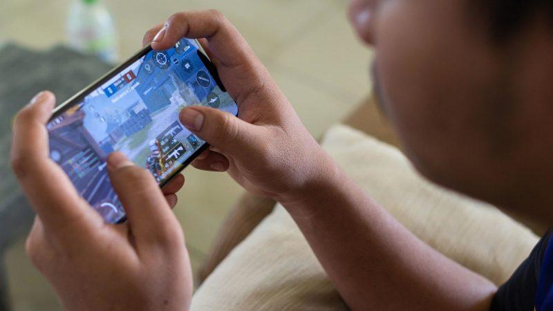 Garoto joga o game PUBG em smartphone. Crédito: Bay Ismoyo/AFP (Getty Images)