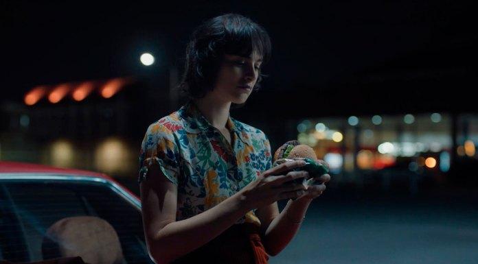 Foto da campanha de Burger King para o Whopper de Plantas. A foto apresenta uma mulher encostada em seu carro, durante a noite, prestes a comer o Whopper de Plantas.