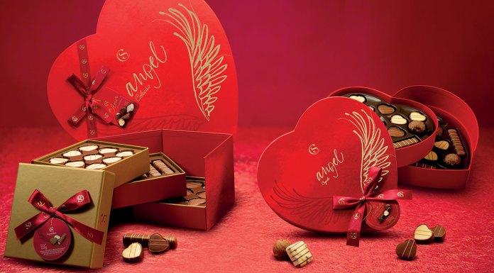 Foto de divulgação da linha de Dia das Mães da Cacau Show. A foto apresenta um fundo e uma mesa na cor vermelha, com as Caixas Angel Coleção, Cupido e Porta-Joias, e alguns bombons de chocolate branco e preto espalhados pela mesa.