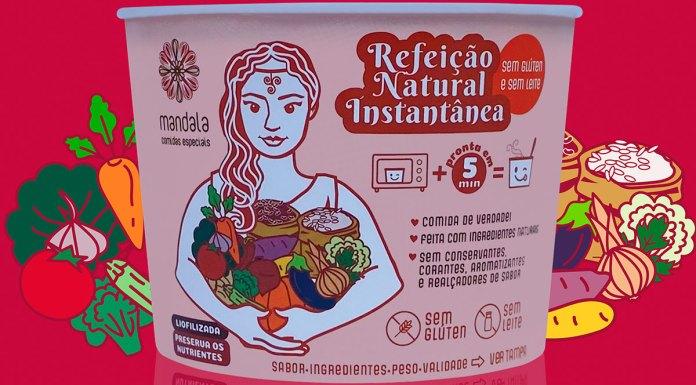 Foto de divulgação da linha de Refeições Naturais Instantâneas da Mandala. Na foto, uma embalagem do produto, e ao fundo vários vegetais desenhados contrastando com um fundo rosa.