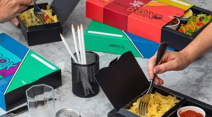 A foto apresenta uma mesa com vários Abbraccio Box espalhados e duas mãos dando uma garfada em dois boxes abertos.