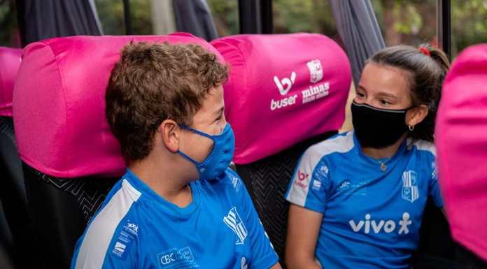 Foto de divulgação para o anúncio do patrocínio da Buser para o Tênis de Minas. A foto apresenta duas crianças com o uniforme da equipe sentadas dentro do ônibus da marca.