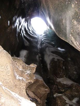 Jak woda może dostać się wgłąb lodowca? Potoki supraglacjalne czasem napotykają na swojej drodze studnie, którymi woda transportowana jest błyskawicznie w dół, umożliwiając powstawanie systemu drenażu in- i subglacjalnego. Zdjęcie pokazuje od spodu małą studnię na lodowcu Horbye. Woda nie wpada przez studnię, ponieważ zdjęcie wykonano już po okresie topnienia. //In a moulin on Horbye glacier (Horbyebreen). Fot. Jakub Małecki 2014//