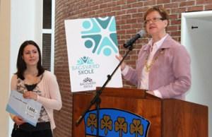 Borgmester Karin Søjberg Holst afslører den nye Bagsværd Skoles logo. Logoets skaber Louise Mie Larsen ses til venstre,  Foto: Gladsaxe Kommune.