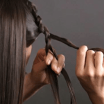 """Part your hair evenly in the middle and make a french braid with a front 3"""" section of your hair."""