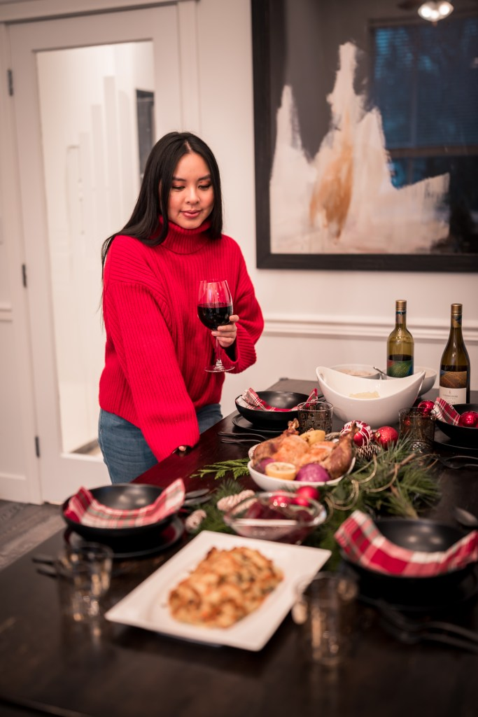 Glamouraspirit admiring her black and plaid holiday table with turkey from meatme and wine from cedar creek winery