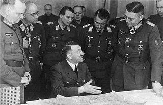 Hitler im März 1945 an der Ostfront in einer Lagebesprechung. Er war gezeichnet von seiner Parkinson-Krankheit und konnte nicht mehr länger als eine halbe Stunde stehen; die zitternde linke Hand ist unter dem Kartentisch verborgen. Neumann&Eberle: