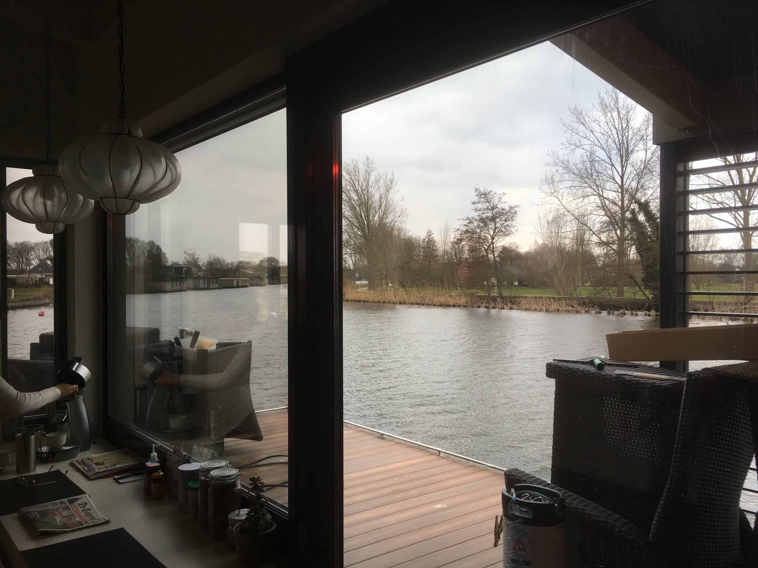 Sunblock Stainless Steel 40 gemonteerd op de ramen van een woonboot teneinde de schittering van het water te verminderen en de zonnewarmte te reduceren