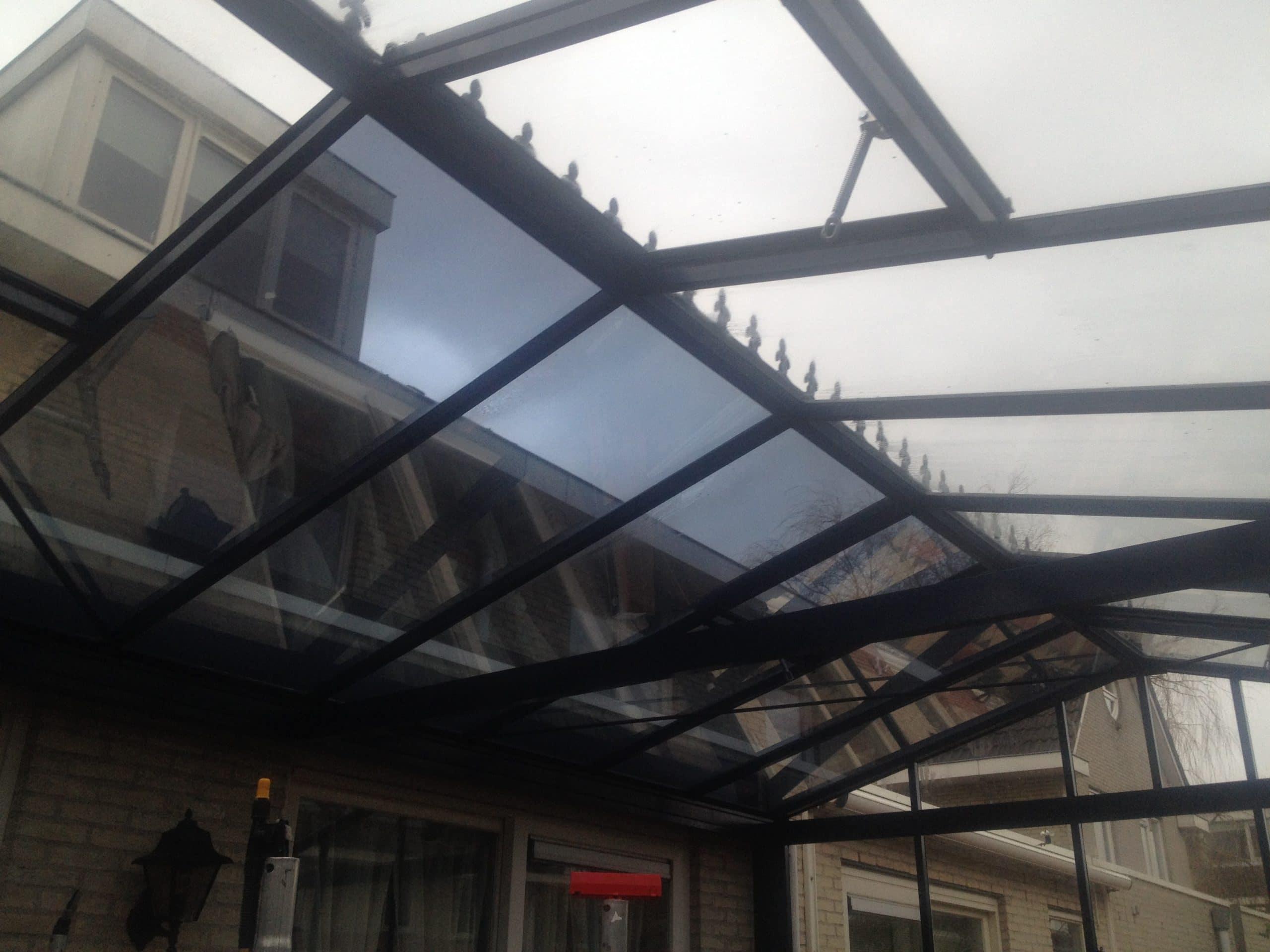 Sunblock Zilver 20 gemonteerd op het glazen dak van een binnentuin - reductie van de zonnewarmte tot 70%