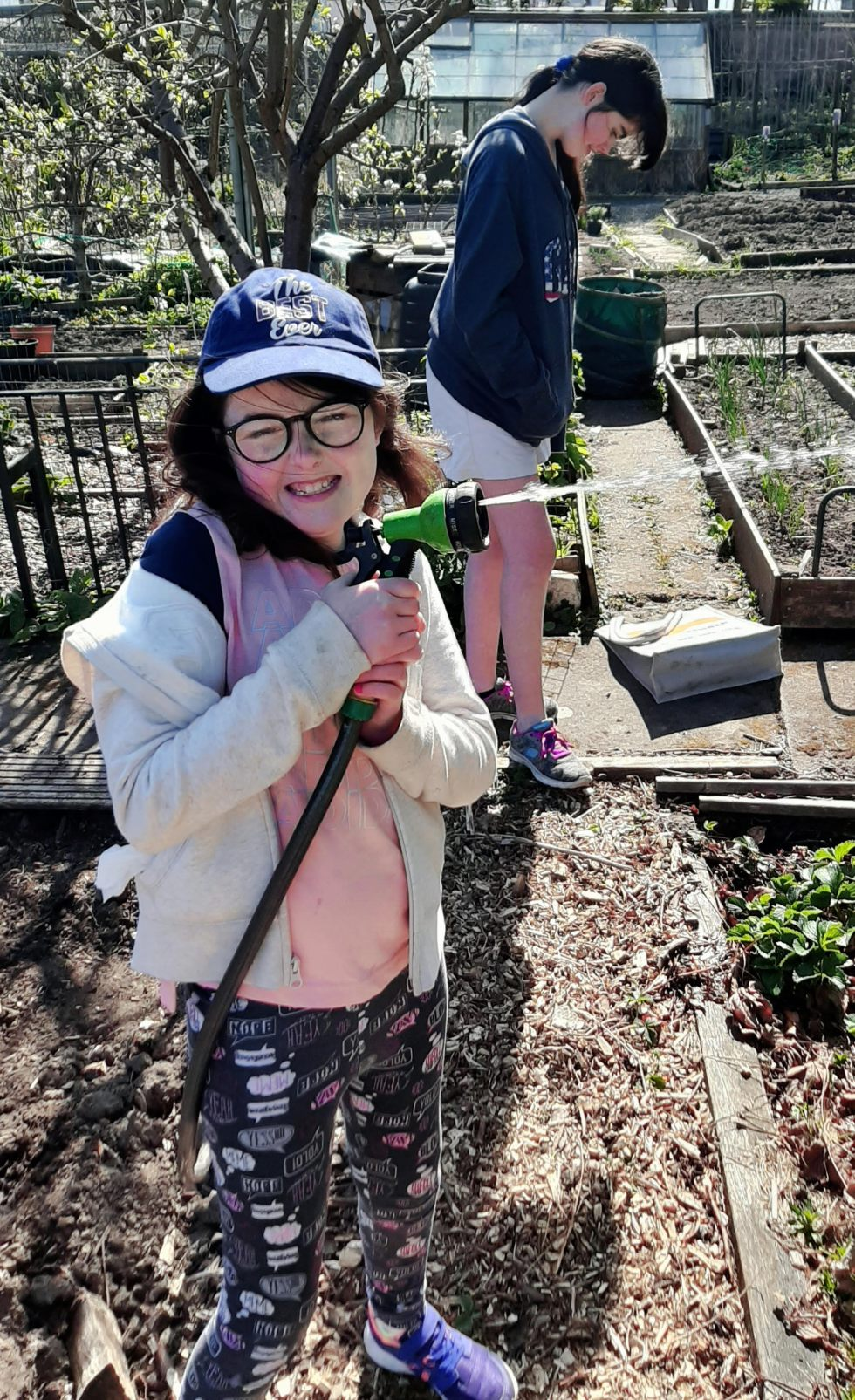 two girls on an allotment; one playing with a water gun hose attachment