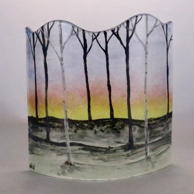 Fused glass curved panel with hand painted birches in front of a sunrise