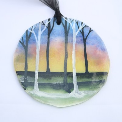 Multicoloured sunrise with tree silhouettes on fused glass