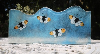 Hand painted orange tip butterflies fused to a turquoise curved glass panel