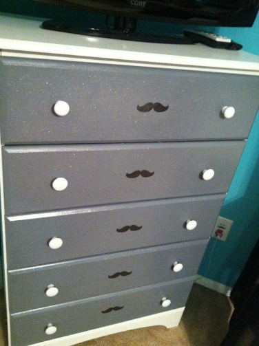 The dressers drawers and knobs were repainted and a mustache was added.