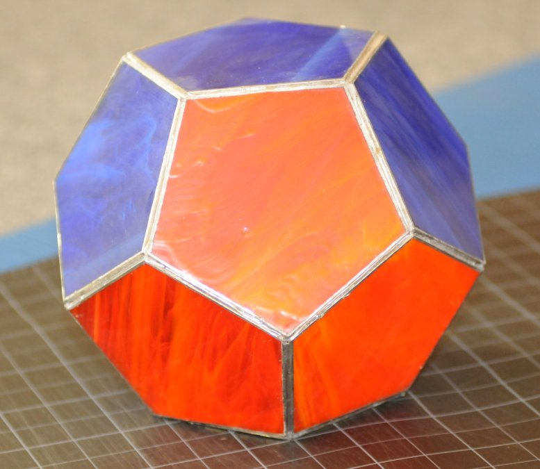 the Platonic Solid Dodecahedron made of blue and orange pentagons of stained glass