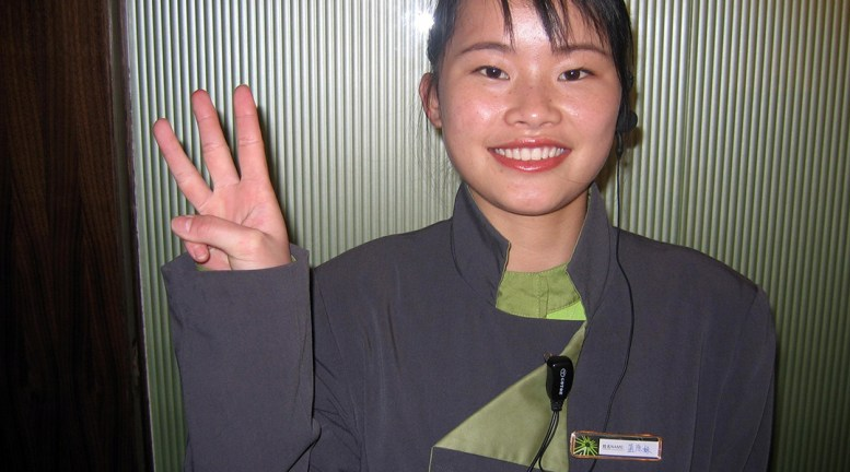 image of a woman dressed in dark purple with green accents giving a 3-finger symbol to the camera