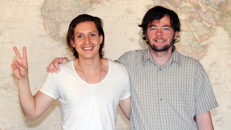Christian and Matt standing together in front of a large world map