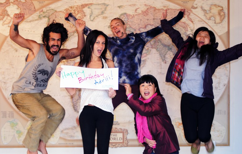 """5 CouchSurfers jump in the air in front of a world map and holding a sign that reads """"Happy Birthday Adriii - Runaway University"""""""