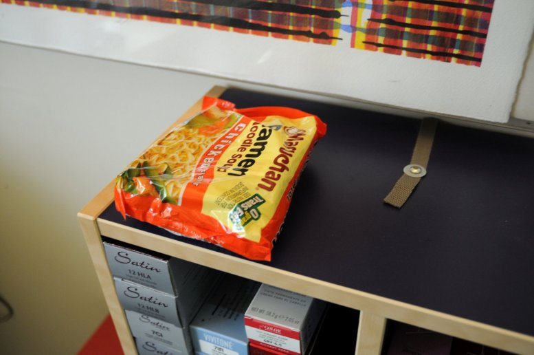 Package of Raman noodles sitting on top of a small shelf