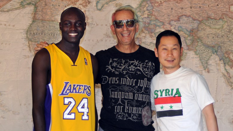 Abdoulaye Sane, Glenn Zucman & Terry Choi stand in front of a large world map. Abdoulaye wears a Laker jersey with #24, Kobe Bryant, Glenn wears a black t-shirt, and Terry wears a white t-shirt with the Syrian flag on it