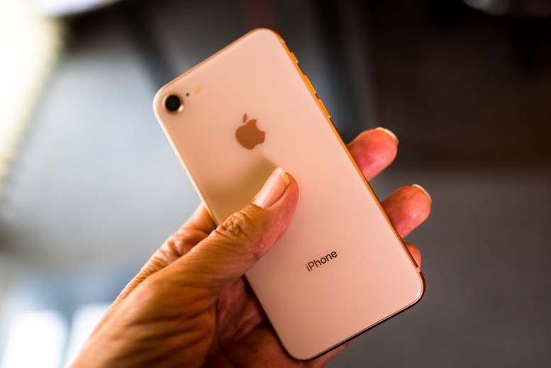 photo of a hand holding a gold iPhone 8 and showing the glass back of the handset