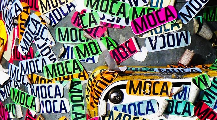"dozens of ""MOCA"" stickers on a street pole"