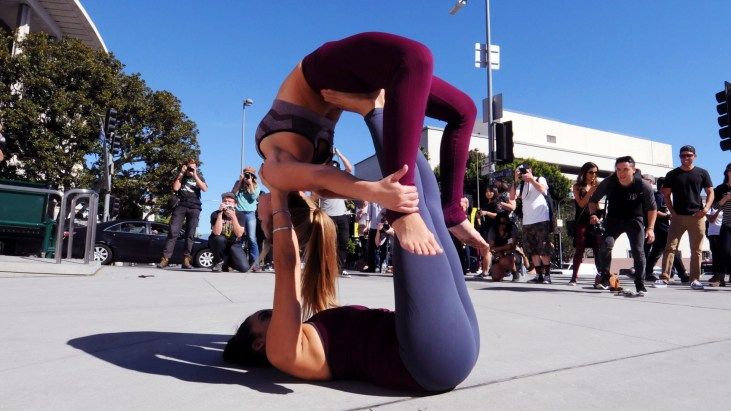 Two dancers making a configuration on the ground in front of Disney Hall on Grand Avenue in Downtown Los Angeles