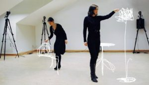 "photo of 2 women in black dresses in a white cube art space ""sketching"" in air with the trace of their movements shown as lines"