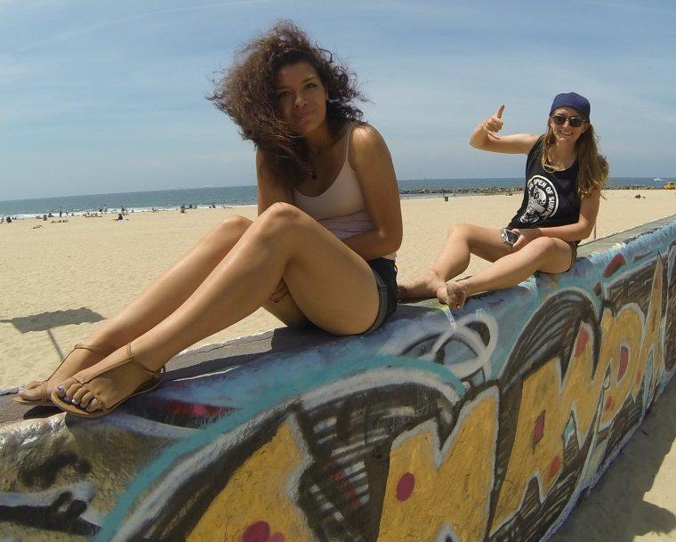 two women sitting on a narrow wall at the Venice Beach Art Walls, Venice Beach, CA