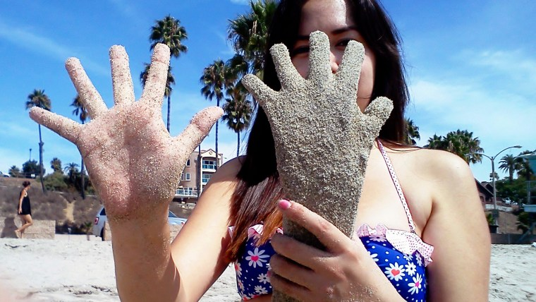 Betty Rodriguez comparing a plaster casting of her hand next to her outstretched hand