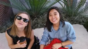 Marina Barnes & Eujin Song sitting on a stone in the CSULB School of Art, Art Gallery Courtyard. Both with smiles. Barnes wearing sunglasses.