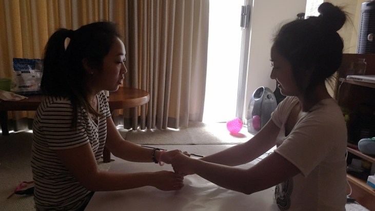 Katherine Shinno with her older sister Melanie making an Automatic Drawing. They sit on the floor facing each other with a sheet of paper between them. In their hands they jointly hold a pencil. They try to relax and let the pencil wander where it will.
