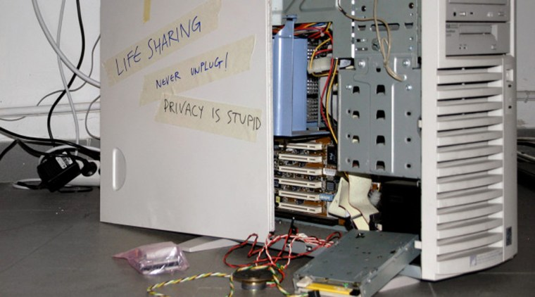 "an open PC computer case with masking tape notes on the side that say ""Lifesharing, Never Unplug, Privacy is Stupid"""