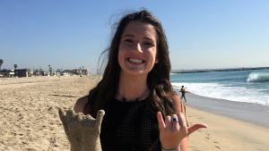 Maddy Braverman at Seal Beach smiling & holding a plaster casting of her hand
