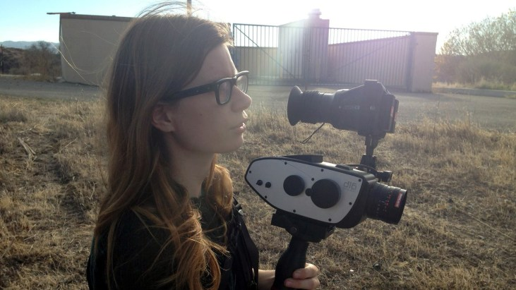 Elle Schneider in a field holding the Digital Bolex camera that she helped create