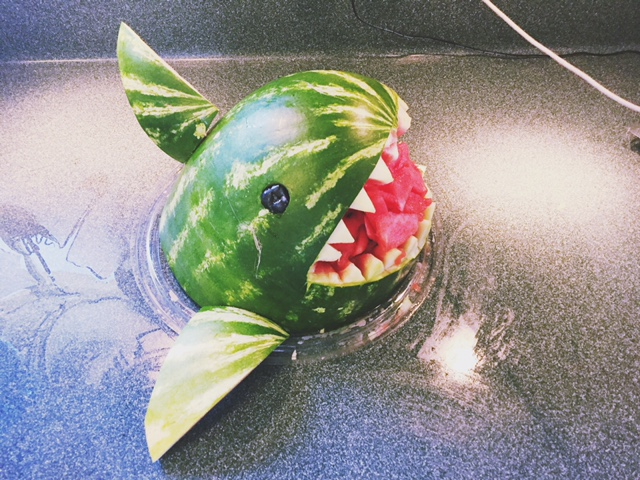 a shark food centerpiece carved out of a watermelon