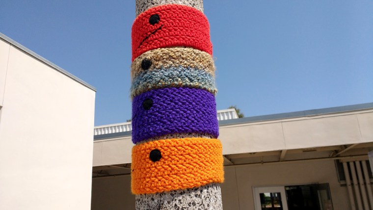 "4 ""collars"" in red, brown, purple, and orange yarn are woven around a light pole at the CSULB, College of the Arts, School of Art, near the Art Gallery Complex"