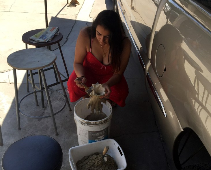 Ana Gomez in her driveway working on a plaster casting of her hand