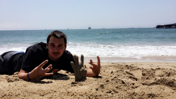 Daniel Schmitz on the beach with a plaster casting of his hand