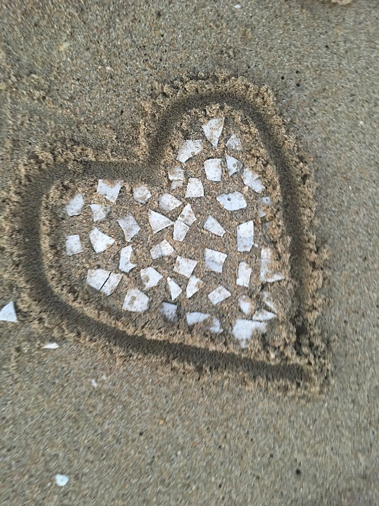 A heart on the beach, made out of bits of sea shells
