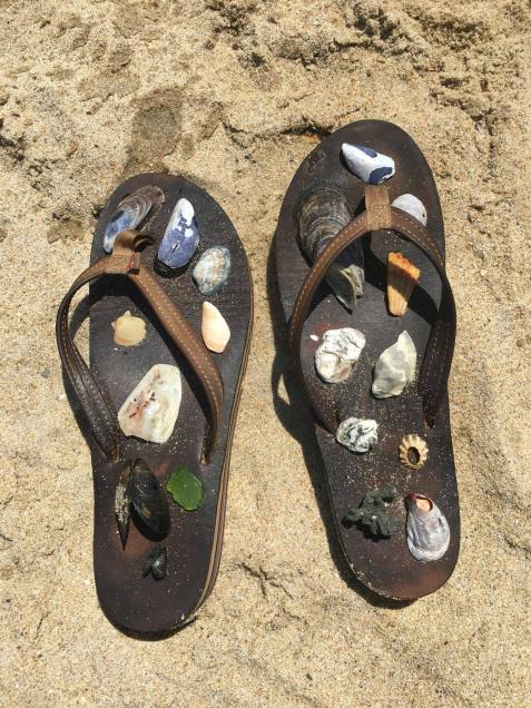 Flip flops on the beach with sea shells on them