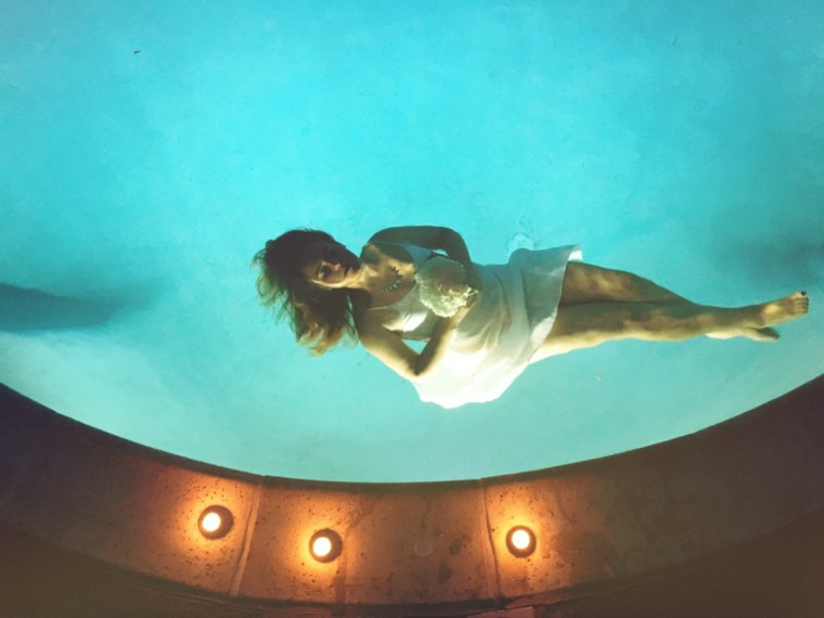 a woman floating, unconscious (simulated) in a pool and holding flowers