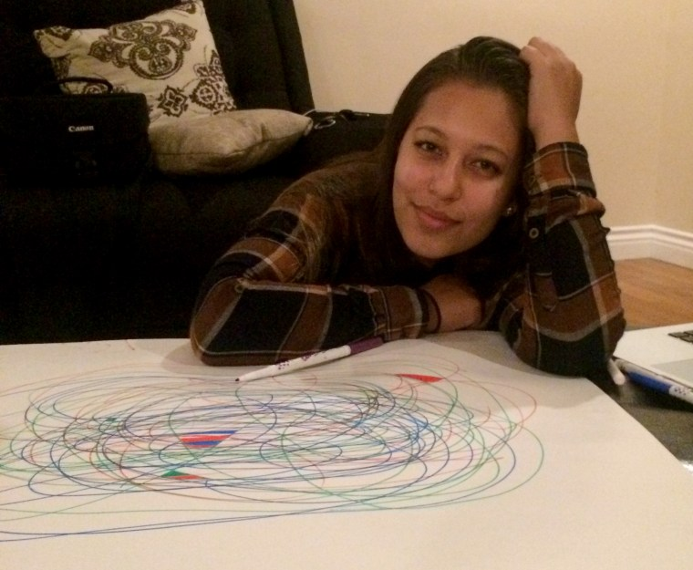 "Briana Garcia leaning over an ""automatic drawing"" or abstract line drawing, that she made with her boyfriend"