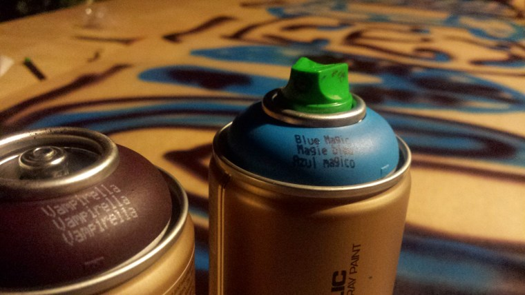 "two cans of Montana Gold spray paint, in the colors""Black Magic"" and ""Vampirella"""