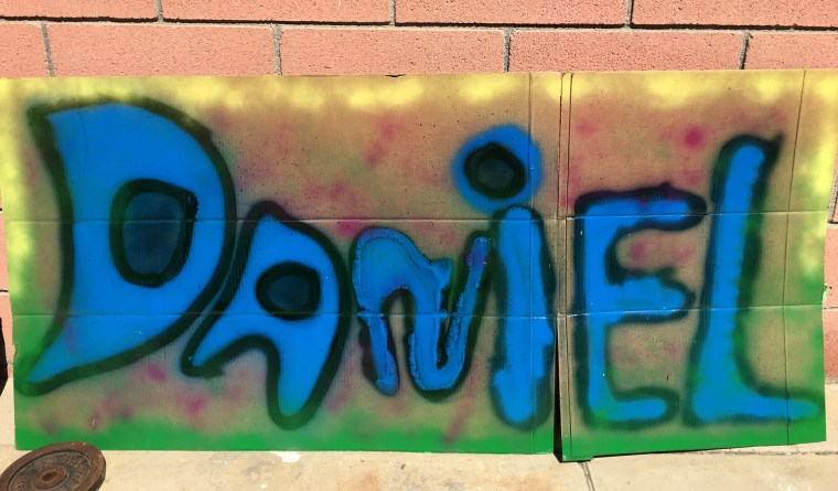 "the name ""Daniel"" in blue spray paint with a black outline and against a background of yellow and green on a large sheet of cardboard"