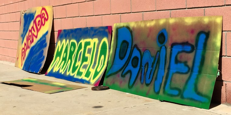 """3 large sheets of cardboard with the spray painted names """"Amanda, Marcelo, Daniel"""""""