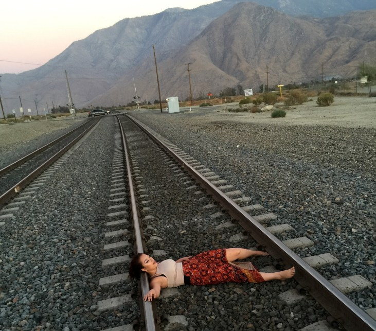 lying on train tracks