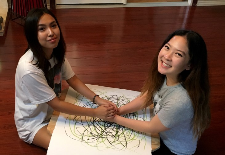 two people sitting across a large sheet of paper and holding a pastel stick together