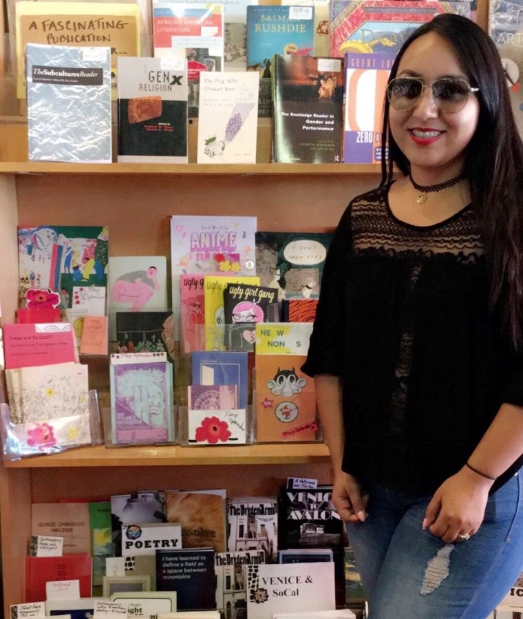 Janett Moctezuma standing in front of many zines and other small, local publications at Small World Books on the boardwalk at Venice Beach, CA