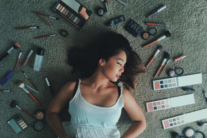 """young person on the floor surrounded by makeup as if all the makeup had """"done her in"""""""